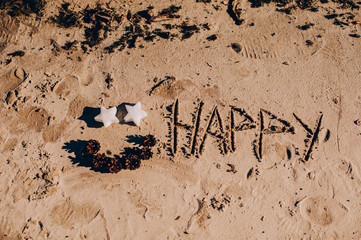 inscription 'HAPPY NEW YEAR' and human footprint in the sand on