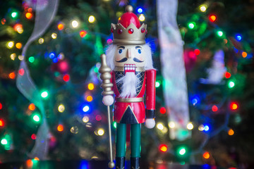 Soldier nutcracker statue standing in front of decorated Christm