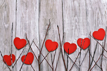 Red hearts in branches on wooden background