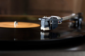 Record player stylus on a rotating disc with orange label