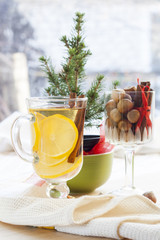 Fresh hot green tea in glass cup with lemon and cinnamon, chocolate cakes in basket and nuts and cinnamon in glass goblet.