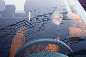 woman waiting in her car in a raining day
