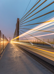Tram lights trails on tram cable-stayed bridge in Krakow, Poland