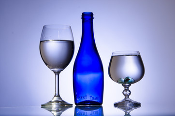 Blue bottle and two stemware of water on white background