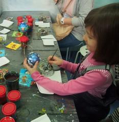 Девочка раскрашивает ёлочную игрушку