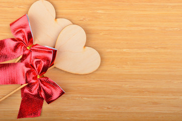 Heart with red bow on wooden background