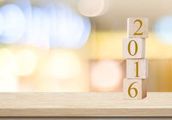 Wooden cubes with 2016 on table over blur background