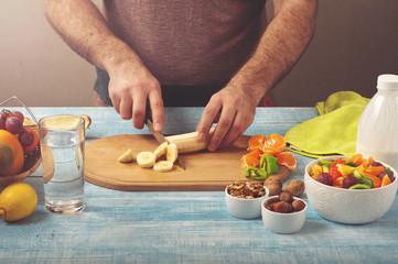 man cooking at home preparing fruit salad