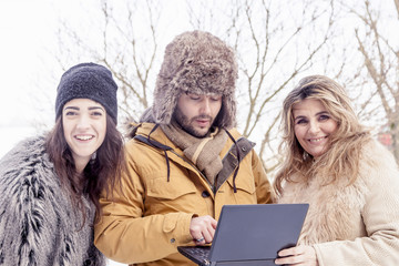 group of friends see a laptop in the snow