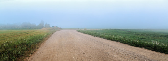 Old gravel rural road in the fog. Rural landscape. Panoramic shot. Toned image.