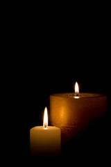 Two burning candles isolated on black background.