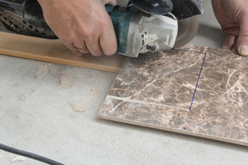 Cutting holes in the tile shaped power tool.