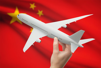 Airplane in hand with flag on background - China