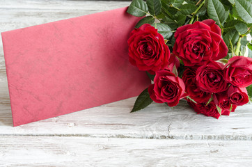 Bouquet of red roses with red wooden plank on table