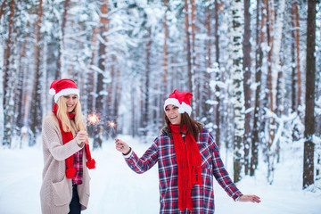 two girls in Christmas hats with sparklers in the winter forest