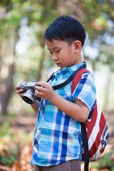 Asian boy checking photos in digital camera.