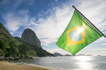 Brazilian flag at Praia Vermelha Red Beach with a sunrise view of Sugarloaf Mountain Pao de Acucar in Rio de Janeiro Brazil