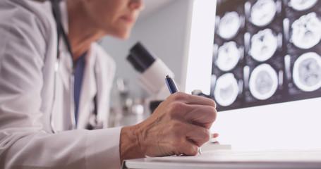 Intelligent female radiologist analyzing with microscope