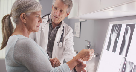 Senior male doctor assessing patient's fractured wrist