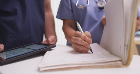 Close-up of mature female nurse writing in a patient's folder