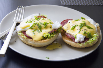Eggs Benedict dish consisting of poached eggs and sliced ham on toasted English muffins, covered with hollandaise sauce against a dark background.