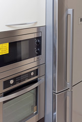 Closeup built-in microwave oven, oven and fridge