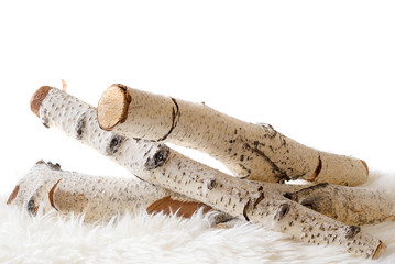 White birch logs on a sheepskin isolated against a white background. High key with copy space