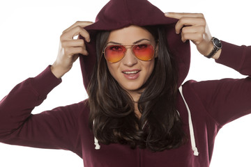 young smiling woman with a hood and sunglasses