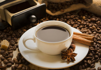 cup of coffee with cinnamon and coffee beans star anise