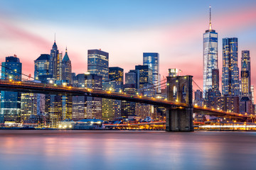 Fotomurales - Brooklyn Bridge at and the Lower Manhattan skyline under a purple sunset