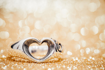Heart ring on the floor with golden bokeh on background