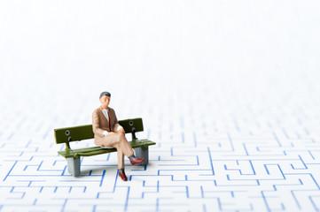 迷路とベンチに座って考えているビジネスマン