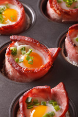 from the oven eggs wrapped in bacon close up in baking dish. vertical