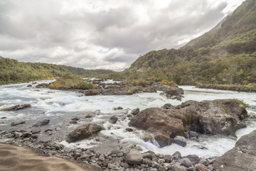 Mountain fast flowing river stream of water in the rocks with cloudy sky