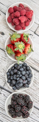Blackberry, strawberry, blueberry and blackberry in white bowl over wooden background