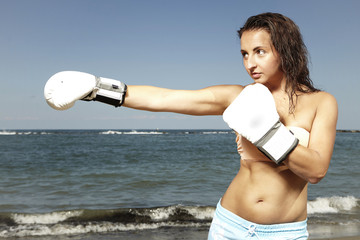 Young brunette woman fighter exercising on beach