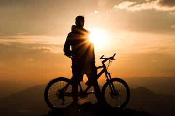 Mountainbiker am Gipfel mit seinem Fahrrad bei Sonnenuntergang
