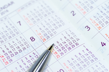 Image of schedule planning, with calendar and pen