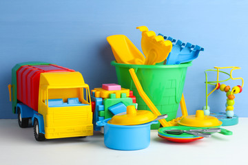 collection of bright toys on wooden table on blue background