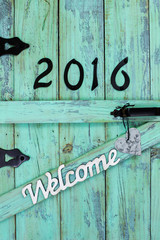 Welcome sign with year 2016 and tin heart on rustic mint green door