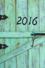 Year 2016 and skeleton key hanging on rustic mint green door