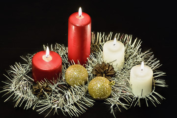 Burning candles on black background with garland