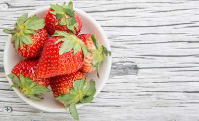 Strawberry fruits in white bowl over wooden background