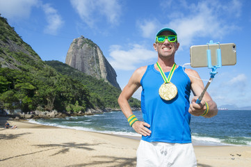 Gold medal athlete posing for a selfie with his mobile phone on a selfie stick at Praia Vermelha Red Beach in Urca, Rio de Janeiro, Brazil