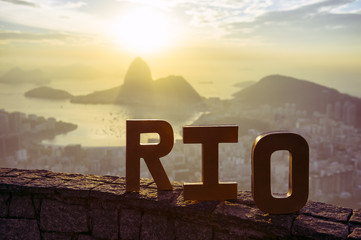 Golden RIO sign standing morning sunrise overlook view of Rio de Janeiro city skyline and Sugarloaf Mountain Wall mural