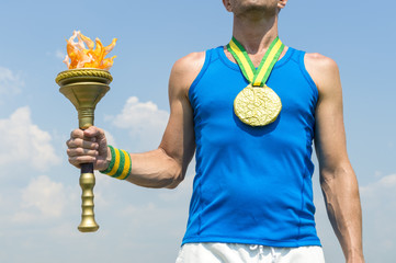 Brazilian gold medal athlete standing with sport torch in front of blue sky in Rio de Janeiro, Brazil