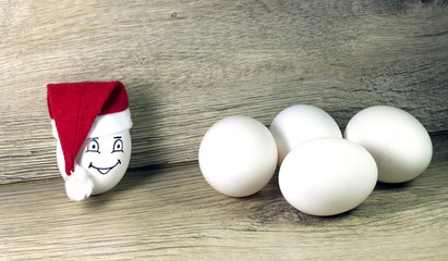 egg in toy christmas hat with drawn emotions