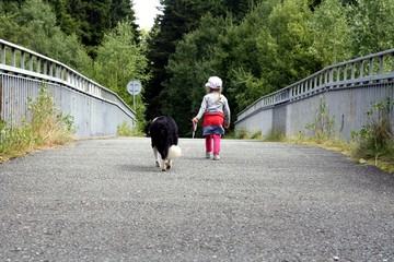 Child and dog for a walk. A little girl and her friend.