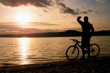 Young man cyclist silhouette on blue sky and sunset above the beach. Biker atthe end of season at lake.