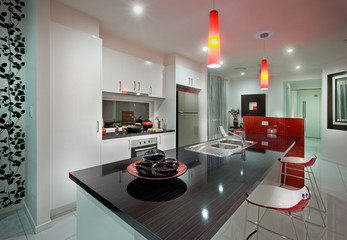 A kitchen with dining table and beautiful red chair